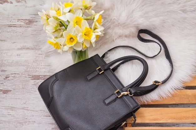 Zwarte vrouwelijke tas op witte vacht, een boeket van narcissen. modieus concept