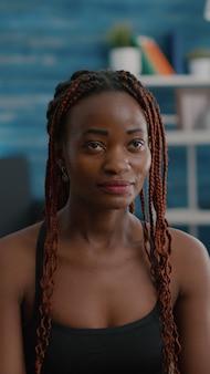 Zwarte vrouwentrainer die in lotushouding op yogamat op vloer met gesloten ogen zit