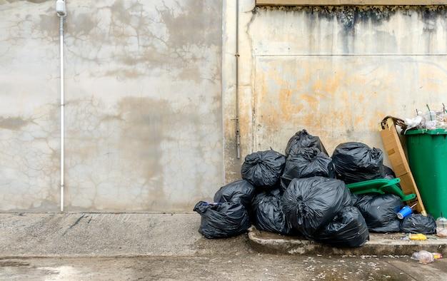Zwarte vuilniszak met oude bakstenen muurachtergrond
