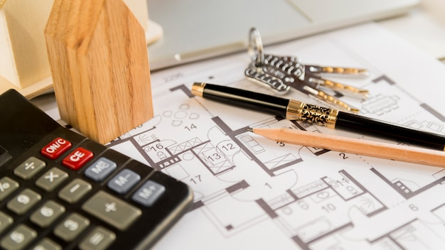 Zwarte vulpen; potlood; toetsen; houten huis blok en rekenmachine op blauwdruk