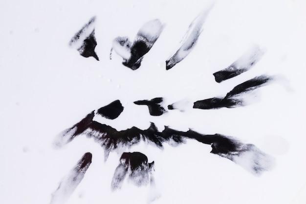 Zwarte waterverfvlekken die op vlotte witte oppervlakte worden geïsoleerd