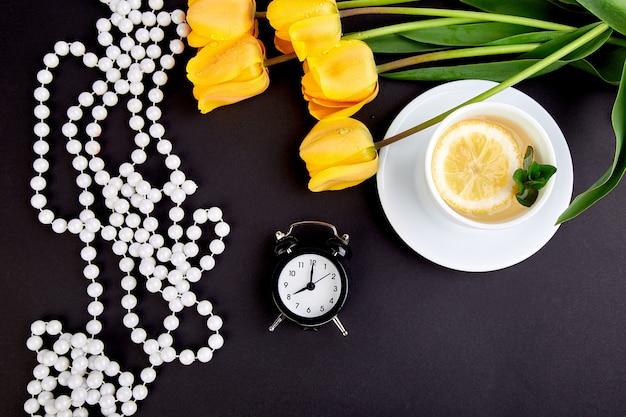 Zwarte wekker dichtbij boeket gele tulpen