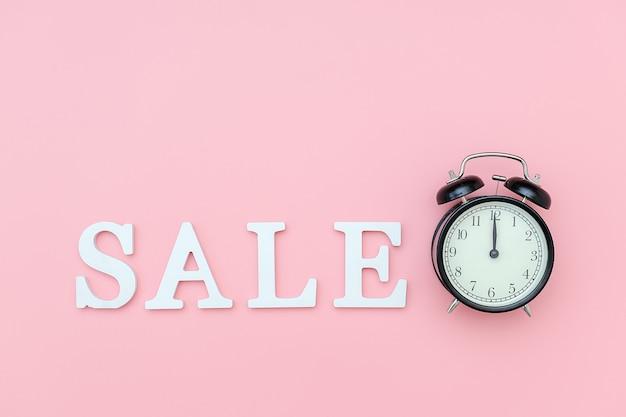 Zwarte wekker en tekstverkoop van witte volumebrieven op een roze achtergrond. zwarte vrijdag, verkooptijd.