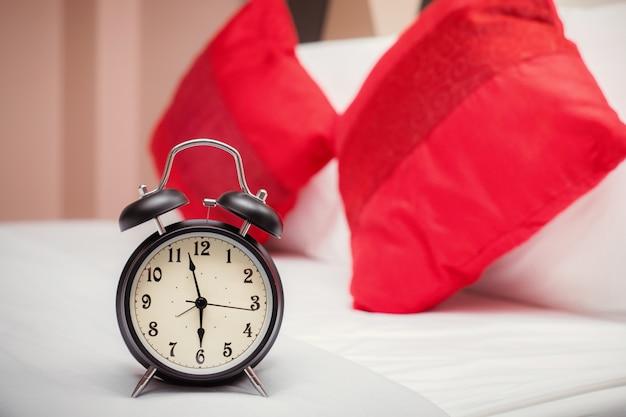 Zwarte wekker in de slaapkamer en met rode kussens