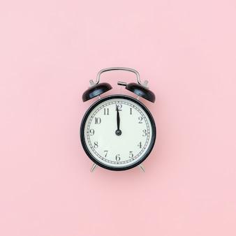 Zwarte wekker in het centrum op roze tafel, close-up. minimalistische stijl kopieer ruimte bovenaanzicht.