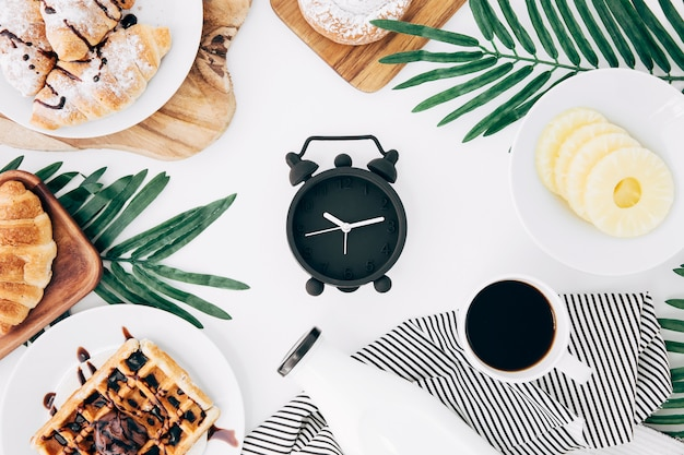 Zwarte wekker omringd met croissant; wafels; bun; koffie; fles en ananas plakjes op witte bureau