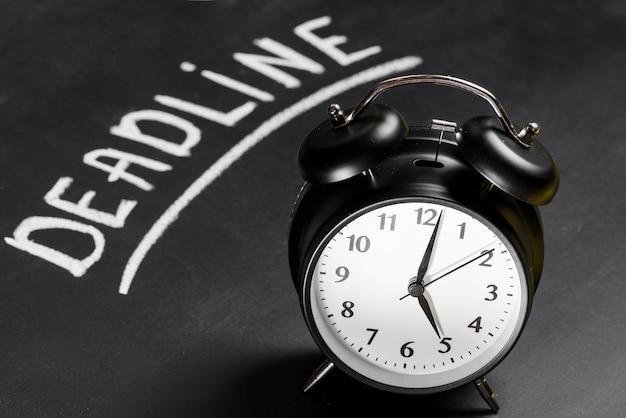 Zwarte wekker op bord met geschreven deadlinewoord