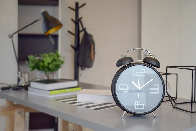 Zwarte wekker op werktafel thuis