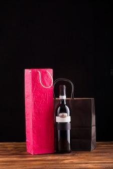 Zwarte wijnfles met mooie papieren zak over houten tafel