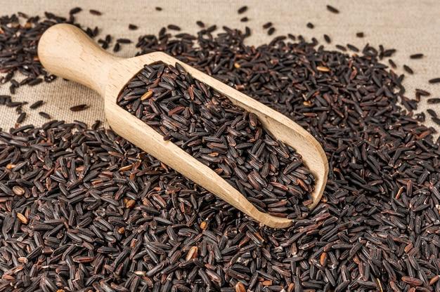 Zwarte wilde rijst en houten lepel in een houten kom. hoop rauwe zwarte wilde rijst.