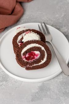 Zwarte woud chocolate cake roll met slagroom en kersen vullen op een grijze achtergrond. kopieer ruimte.