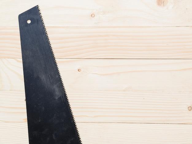 Zwarte zaag op houten tafel