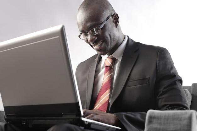 Zwarte zakenman die aan laptop werkt