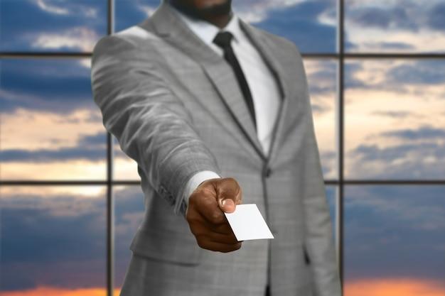 Zwarte zakenman die bezoekkaart geeft. man met kaart bij zonsopgang. makelaar in onroerend goed op het werk. advocaat kwam naar het zakencentrum.
