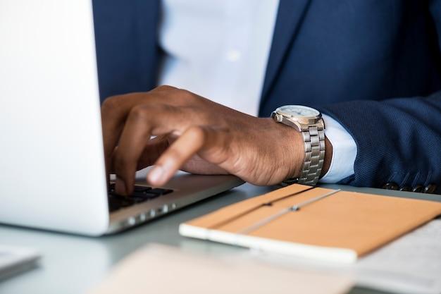 Zwarte zakenman die computerlaptop met behulp van