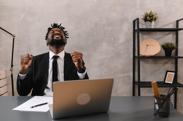 Zwarte zakenman die laptop gebruikt voor het analyseren van gegevensbeurs