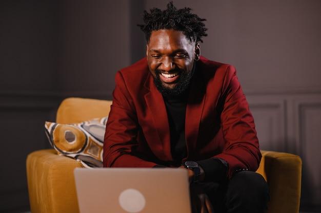 Zwarte zakenman die laptop gebruikt voor het analyseren van gegevensvoorraad