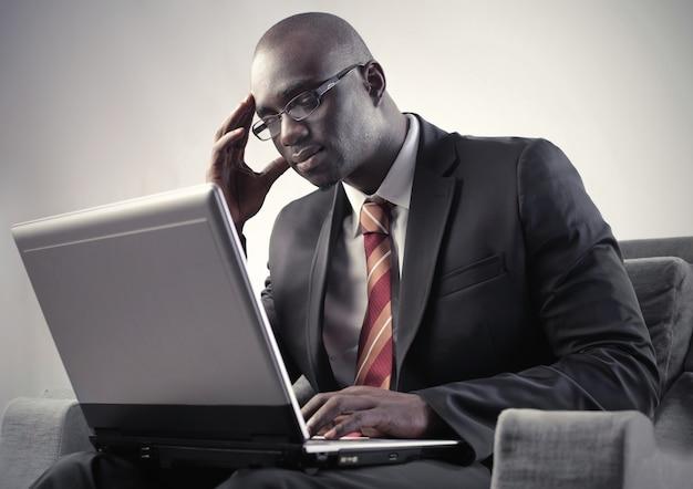 Zwarte zakenman die laptop met behulp van