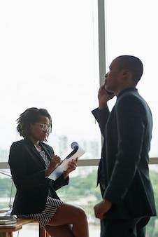 Zwarte zakenman die op telefoon spreekt en vrouwelijke collega die op blocnote schrijft