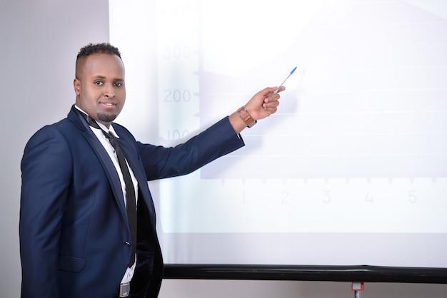 Zwarte zakenman die presentatie geeft aan zijn collega's.