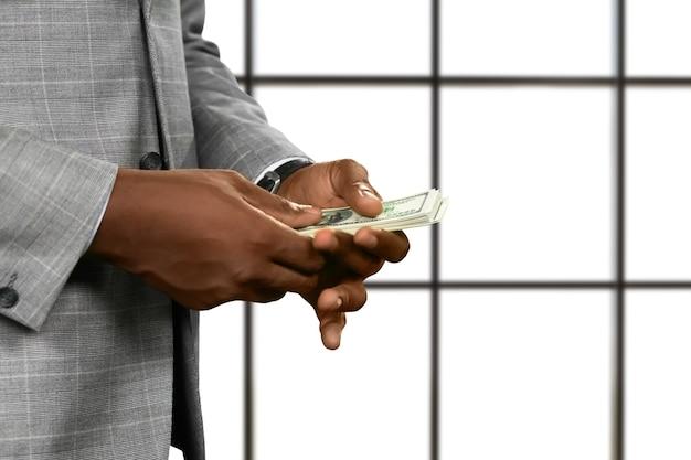 Zwarte zakenman handen met geld. amerikaanse dollars op witte achtergrond. het is nooit genoeg. altijd op jacht naar succes.