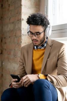 Zwarte zakenman met afro-kapsel zittend op de vensterbank en zoekend naar nummer op smartphone terwijl hij naar muziek luistert in een draadloze koptelefoon