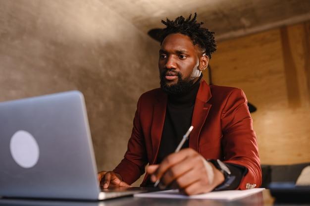 Zwarte zakenman met behulp van laptop voor het analyseren van gegevensbeurs