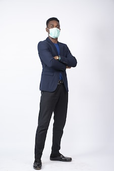 Zwarte zakenman met een pak en gezichtsmasker met gekruiste armen - het nieuwe normale concept