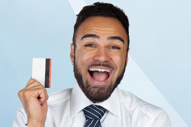 Zwarte zakenman met gelukkige uitdrukking die zijn creditcard toont
