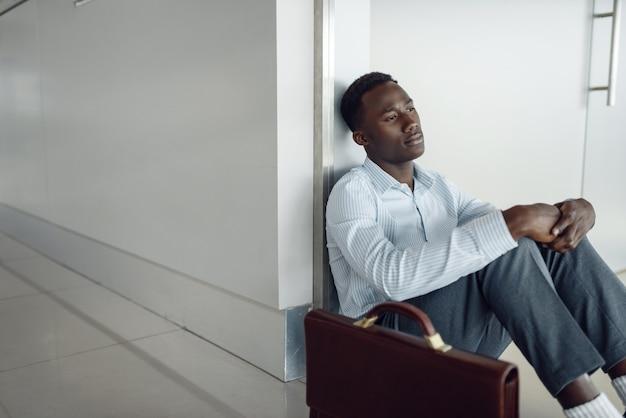 Zwarte zakenman met werkmap zittend op de vloer in de gang van het kantoor. moe zakenman ontspannen in gang, zwarte man in formele kleding
