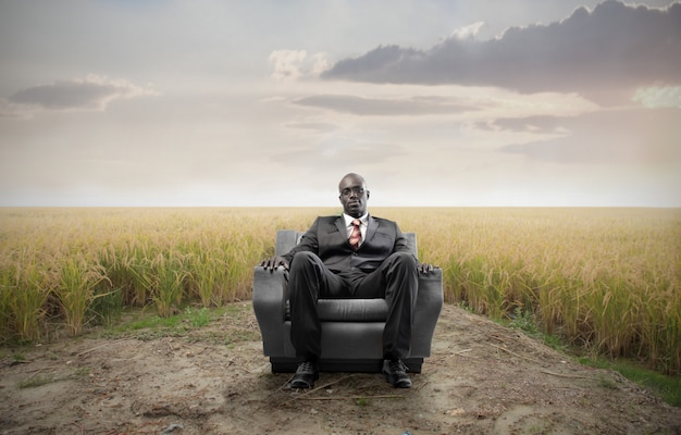 Zwarte zakenman zitten in een leunstoel