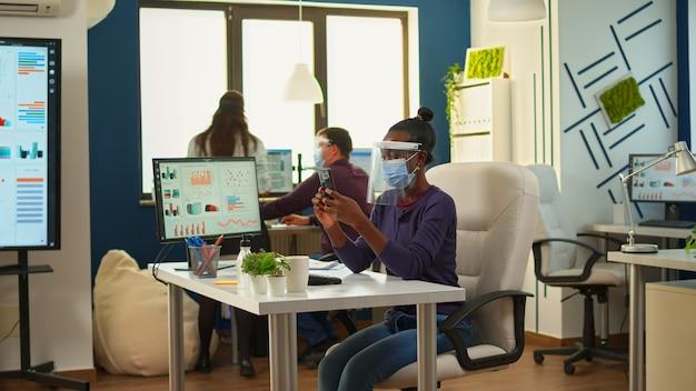 Zwarte zakenvrouw browsen met smartphone zittend in kantoorruimte met gezichtsmasker en vizier terwijl team stategy doet. multi-etnische collega's die werken met respect voor sociale afstand in een financieel bedrijf