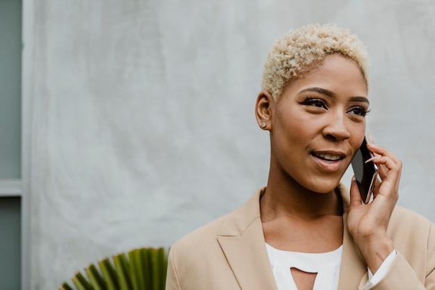 Zwarte zakenvrouw die aan de telefoon spreekt
