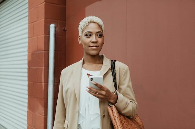 Zwarte zakenvrouw die haar mobiel gebruikt