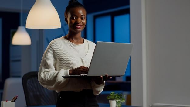 Zwarte zakenvrouw die lacht naar de voorkant en een laptop vasthoudt die 's avonds laat in de buurt van een bureau in een start-up bedrijf staat