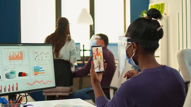 Zwarte zakenvrouw met gezichtsbescherming tegen covid-19 pandemie met online vergadering op smartphone zittend op moderne werkplek. multi-etnische collega's die werken met respect voor sociale afstand in bedrijven