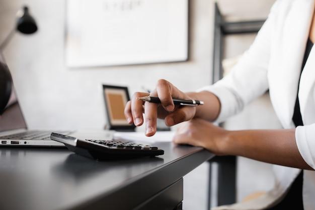 Zwarte zakenvrouw rekent op een rekenmachine en maakt aantekeningen financier of accountant werkt vanuit huis