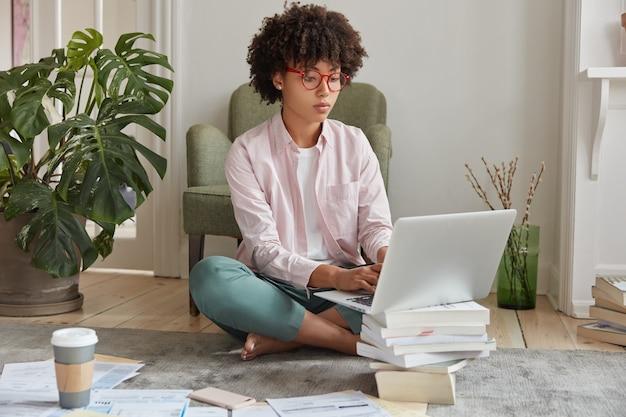 Zwarte zakenvrouw toetsenborden op laptopcomputer, maakt diploma papier
