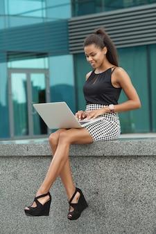 Zwarte zakenvrouw zitten in de financiële stad, met behulp van een laptopcomputer, doordachte, zonnige buitenshuis.