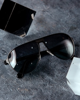 Zwarte zonnebril op het grijze oppervlak
