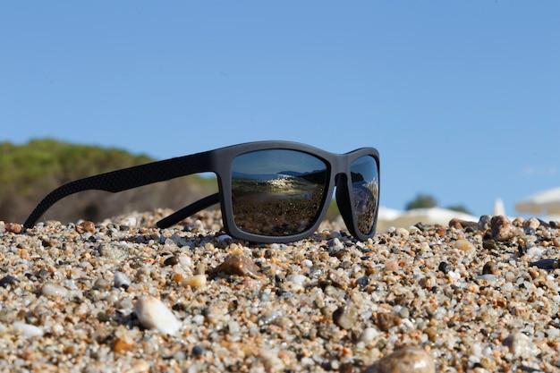 Zwarte zonnebril op kiezelsteen en hemelachtergrond
