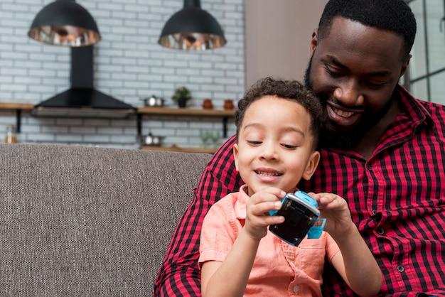 Zwarte zoon en vader zitten met speelgoedauto