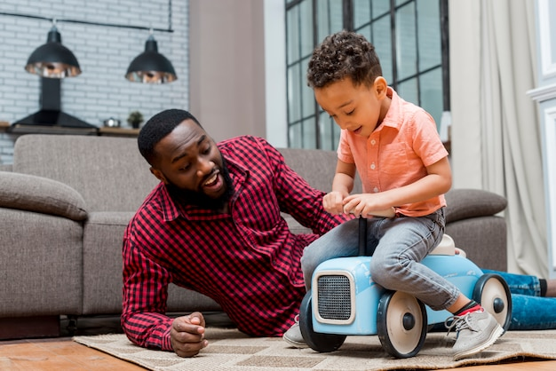 Zwarte zoon rijden speelgoedauto met vader