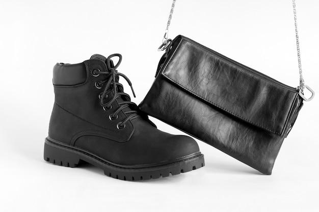 Zwarte zware vrouwelijke laarzen en modieuze lederen clutch op wit