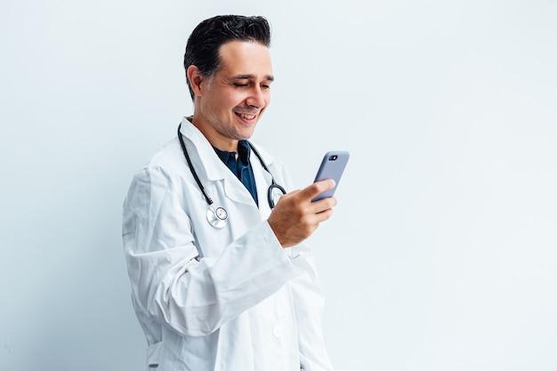 Zwartharige arts die witte jas en stethoscoop draagt die zijn mobiele telefoon bekijkt en glimlacht terwijl hij een videogesprek voert, op witte achtergrond.