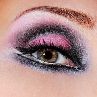 Zwartviolette make-up van ogen. groene ogen. macro een foto van een oog.