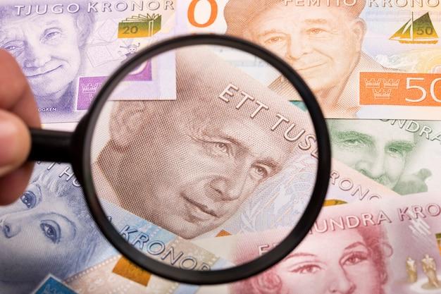 Zweedse kronen in een vergrootglas een bedrijfsachtergrond