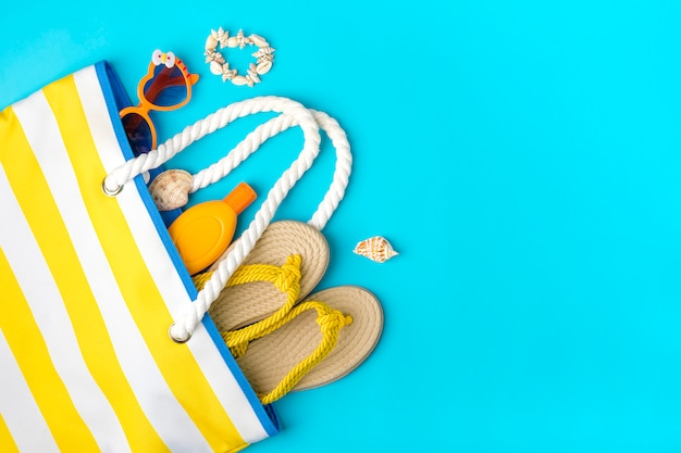 Zwemaccessoires - trendy strandtas met sunblock strepen, hartvormige bril, gele flip flop, schelpen op blauwe achtergrond plat leggen