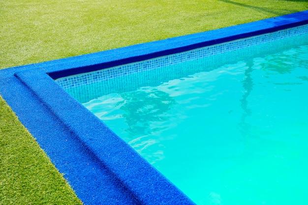 Zwembad aan de rand van het zwembad is kunstgras groen gras