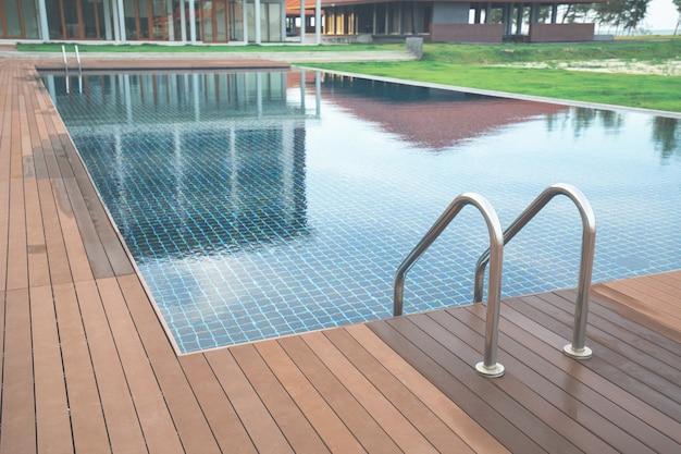 Zwembad bij hotel met trap en houten dek op het strand.